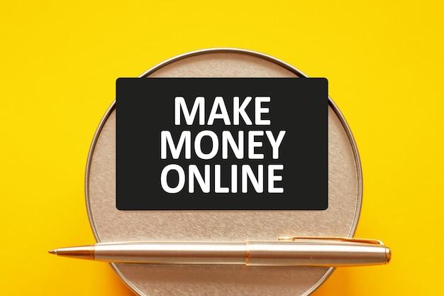 돈을 온라인으로 만드십시오-종이에 하얀 글자를 쓰는 단어. 둥근 금속 스탠드와 금속 쓰기 펜 노란색 배경에 텍스트와 함께 검은 카드. 비즈니스, 금융 및 교육 개념