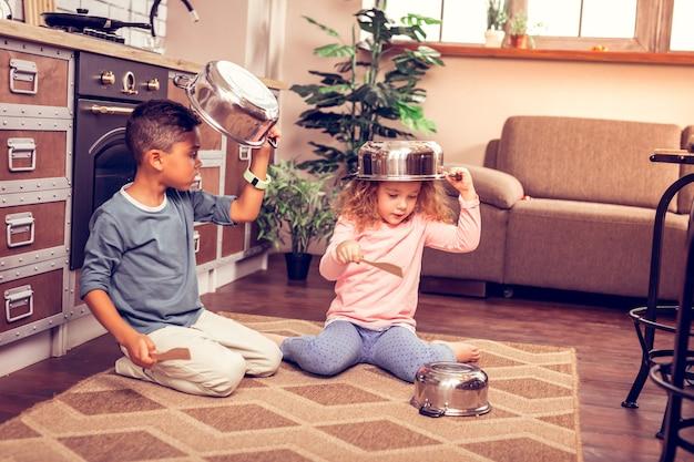 音楽を作ります。頭の上に鍋を持ちながら台所用品を見るかわいい巻き毛の女の子