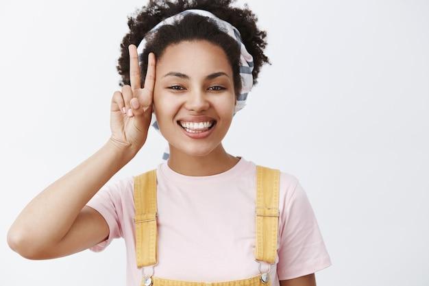 스트레스를받지 말고 평화를 만드십시오. 노란색 바지와 머리띠에 평온한 매력적이고 편안한 아프리카 계 미국인 여성의 초상화가 얼굴 근처에 승리 제스처를 보이고 자랑스럽고 행복하게 웃고 있습니다.