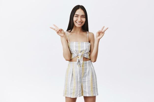 戦争ではなく平和を作りなさい。トップスとショートパンツを合わせて長い黒髪の魅力的なファッショナブルなアジアの女性モデルの肖像画、勝利の兆候を示し、広く笑って、プロフィール写真のポーズをとる
