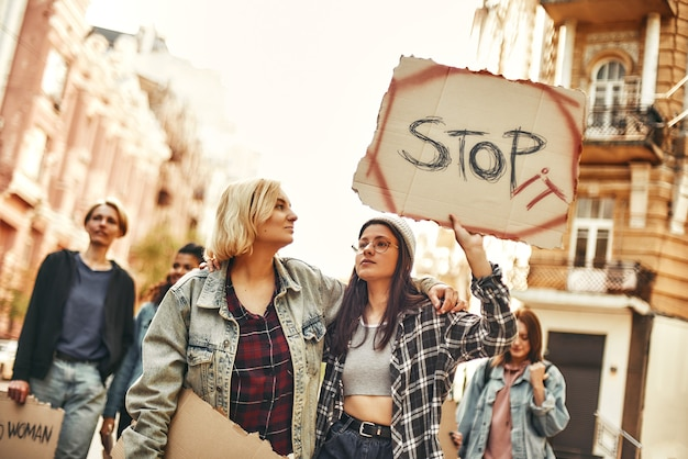 Make peace young woman in eyewear and casual clothing is holding a banner with word