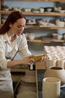 Сделайте фото. молодая рыжая женщина фотографирует горшки в мастерской