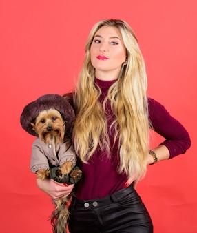 犬が服を着て快適に感じることを確認してください。アパレルとアクセサリー。どの犬種がコートを着るべきか。女の子はコートで小さな犬を抱きしめます。女性はヨークシャーテリアを運びます。寒さのためのドレッシング犬。
