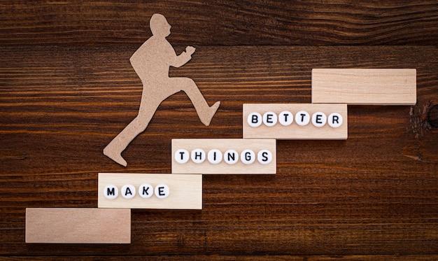 Сделать лучше - концепция улучшения. бумажный человек, поднимающийся по ступеням к успеху в концептуальном изображении на деревянном фоне.