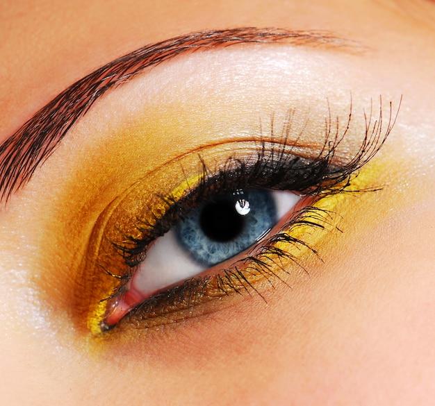 メイクアップ–ファッションの明るい黄色のアイシャドウ。