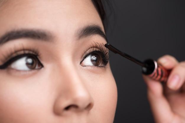 메이크업 및 화장품 개념입니다. 그녀의 메이크업 속눈썹 블랙 마스카라를 하 고 아시아 여자.
