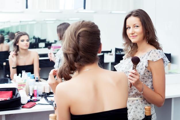 거울 앞에서 일하는 메이크업 아티스트와 모델, 카메라를 바라보는 mua에 선택적 초점