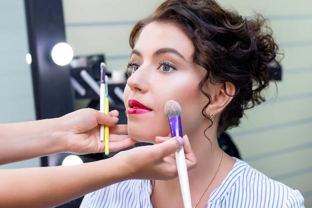 Визажист наносит легкий слой матовой пудры с помощью профессиональной кисти для макияжа. девушка у визажиста