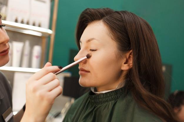 메이크업 아티스트는 메이크업 브러시로 고객의 피부에 파우더를 바릅니다. 미용실에서 메이크업 과정