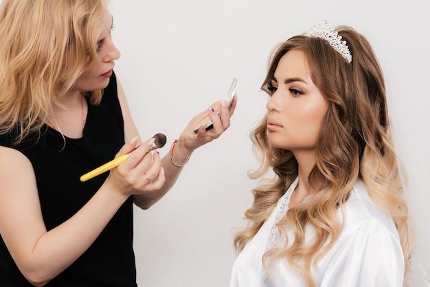 Визажист наносит пудру на лицо девушки-невесты в профессиональном салоне красоты