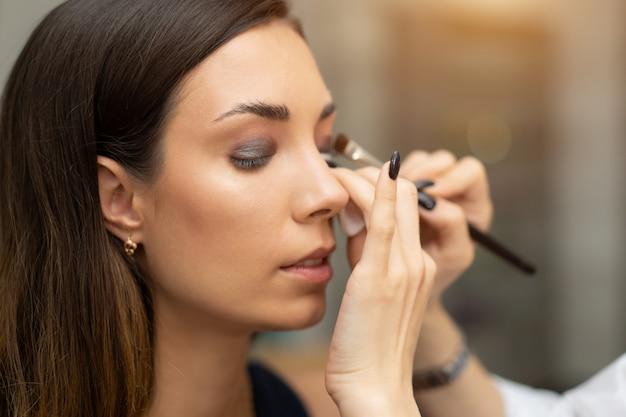 Make-up artist applying bright base color eyeshadow