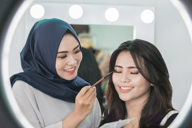 Make-up artist applying cosmetic