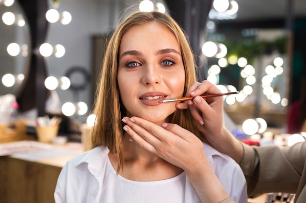 Make-up artist applying lipstick on smiling woman with brush