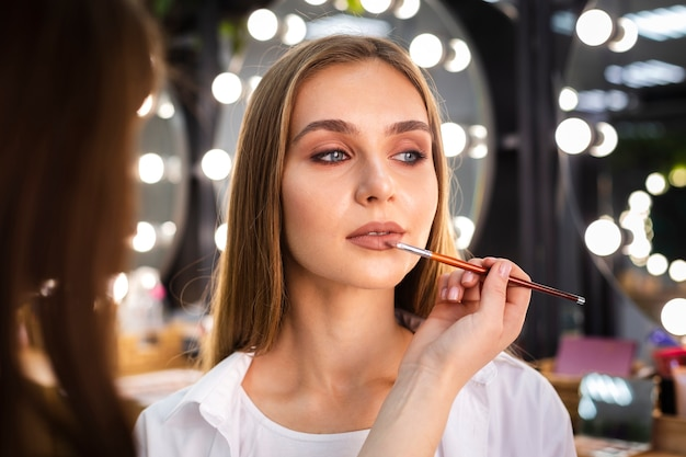 Make-up artist applying lipstick on woman with brush