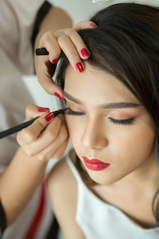 Make-up artist applying liquid eyeliner with brush