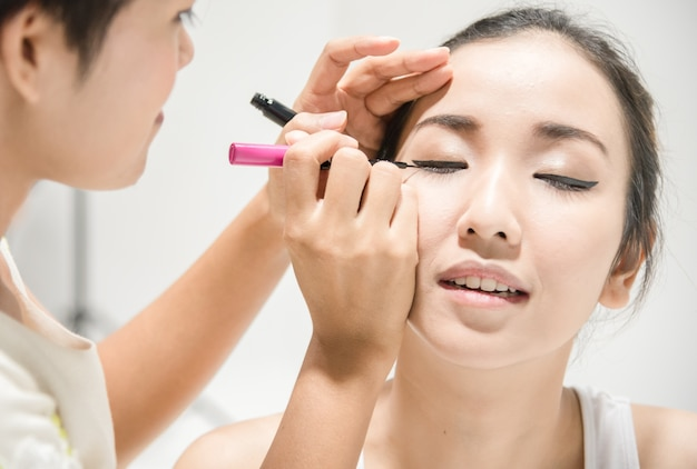 Make up artist applying make up to clean face a fashion model or bride