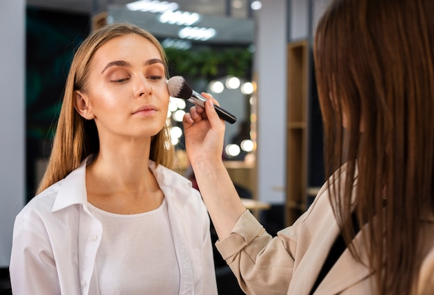 Make-up artist applying powder on face with brush