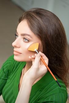 美しい若い白人女性の顔に色調の基礎のプロのメイクアップを適用するメイクアップアーティスト