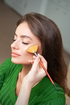 Визажист наносит профессиональный макияж тональной основы на лицо красивой молодой кавказской женщины