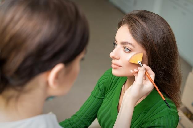 Визажист, наносящий профессиональный макияж тональной основы