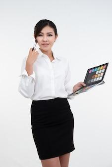 メイクアップアーティストのアジアの女の子は、白で隔離されるメイクをした化粧品の製品を示しています。美の概念