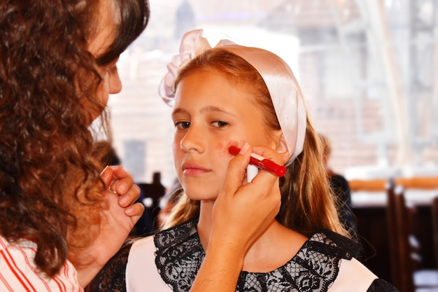 Make-up artist does makeup to a young girl model.