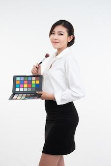 メイクアップアーティストの女の子は、メイクアップされた化粧品の製品を示しています。美の概念