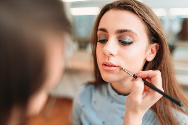 女性の唇に光沢を適用するアーティストの手を構成します。