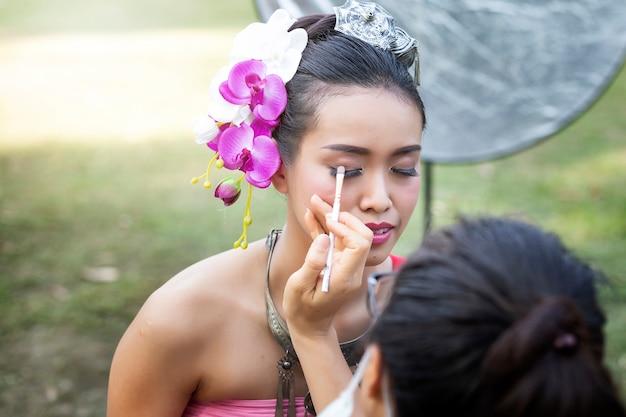 Make up artist making up eye liner to thai woman wearing thai traditional clothing