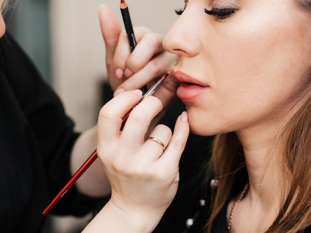메이크업 아티스트는 미용실에서 여자를위한 립 브러쉬로 입술을 페인트