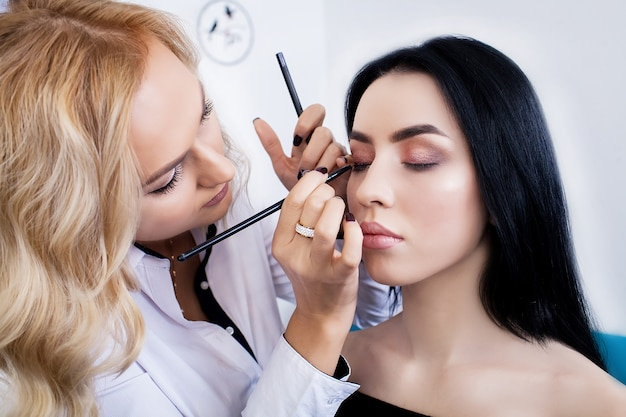 Make-up artist preparing beautiful bride for ceremony in a morning