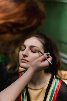 메이크업 아티스트가 메이크업을합니다. 여자는 눈꺼풀에 그림자를 바르고 눈썹과 눈을 가져옵니다.