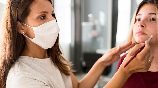 クライアントでの作業中に医療マスクを身に着けているメイクアップアーティスト