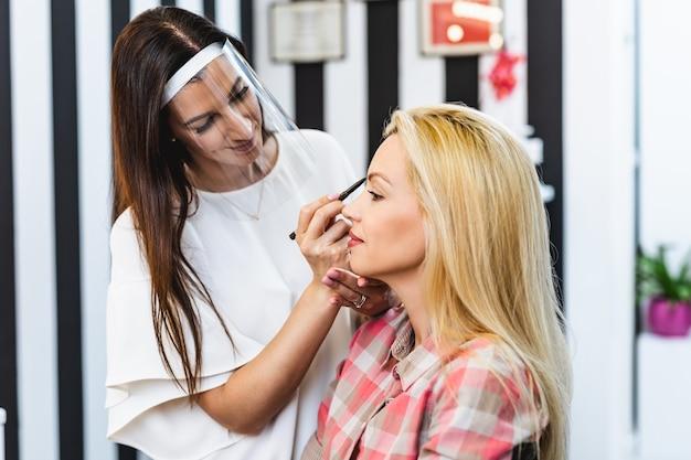 아름다운 중년 금발 여성에게 전문적인 메이크업을 적용하는 얼굴 보호 마스크와 방패를 가진 메이크업 아티스트. 코로나바이러스 전염병 라이프 스타일.