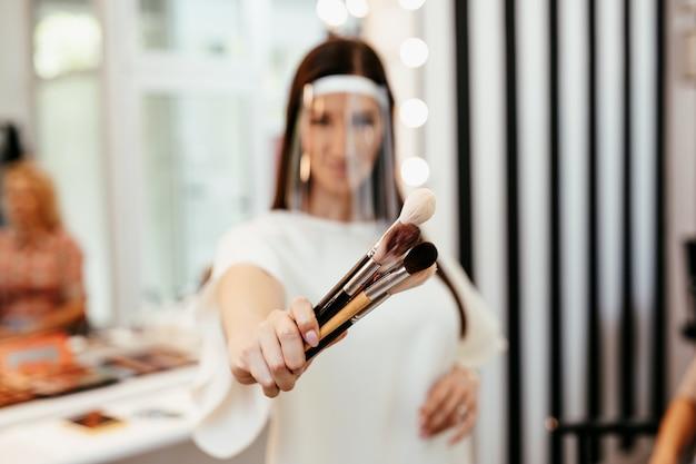 아름다운 중년 금발 여성의 전문적인 메이크업을 적용하는 얼굴 보호 마스크로 메이크업 아티스트. 코로나바이러스 전염병 라이프 스타일.