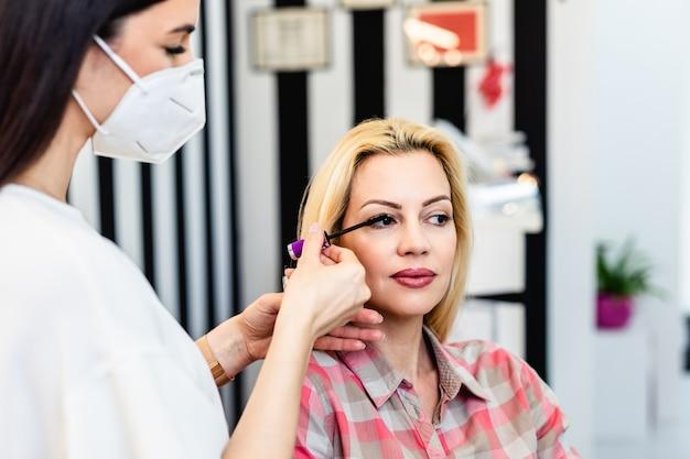 美しい中年のブロンドの女性のプロのメイクアップを適用する顔の保護マスクでアーティストをメイクアップします。コロナウイルスのパンデミックライフスタイル。