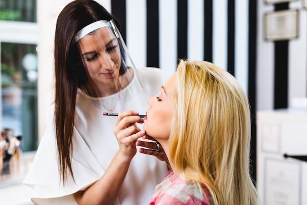 아름다운 중년 금발 여성에게 전문적인 메이크업을 적용하는 얼굴 보호 방패로 아티스트를 구성하세요. 코로나바이러스 전염병 라이프 스타일.