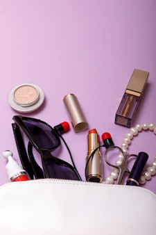 Make up bag with cosmetics isolated on pink background
