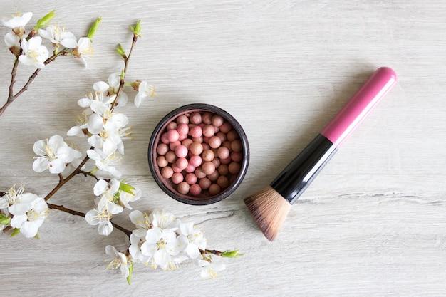 메이크업 볼은 피부 관리를 위해 천연 화장품을 블러셔합니다. 나무 테이블에 꽃이 만발한 벚꽃의 장식. 미용 및 스파 개념