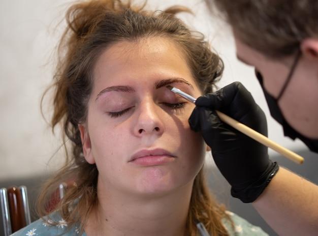 Визажист-косметолог наносит на брови краску хной. профессиональный уход за лицом.