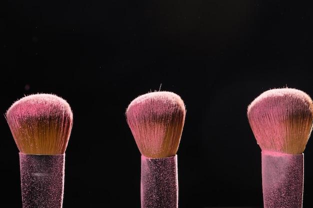메이크업, 미용 및 미네랄 화장품 컨셉 브러쉬, 검은 벽 위에 핑크 파우더