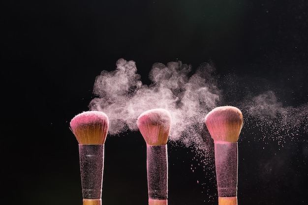 メイクアップ、美容、ミネラル化粧品のコンセプト-ピンクのパウダーを別のものからブラシで払い落とします