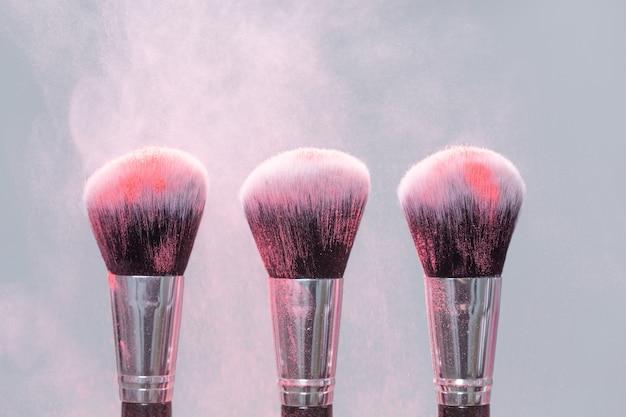 Макияж, красота, минеральная косметическая концепция. кисть с розовой пудрой на светлом фоне