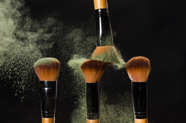 Make up, beauty and mineral powder concept - cosmetics brush and explosion colorful makeup powder