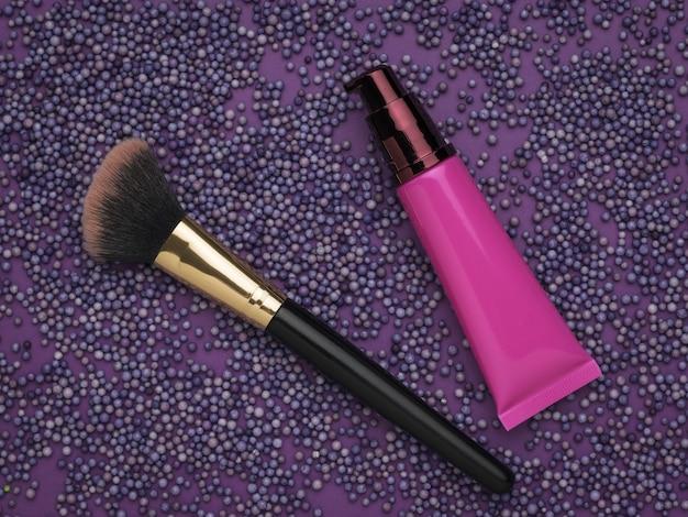 Кисть для макияжа и косметический крем над фиолетовыми шариками. набор для ухода за лицом.
