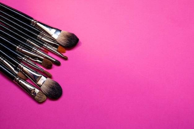 Кисть для макияжа лежит на розовом фоне.