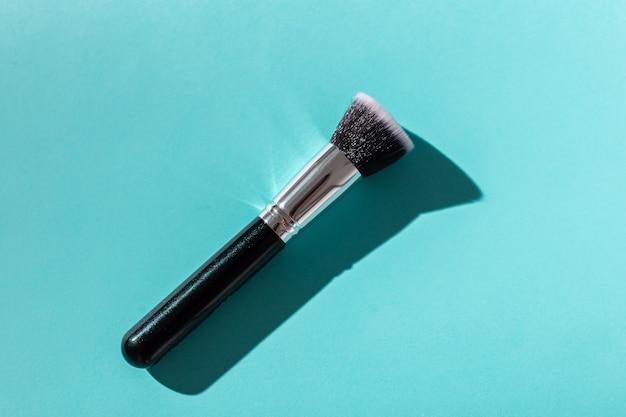 Кисть для макияжа на бирюзовом фоне, вид сверху.