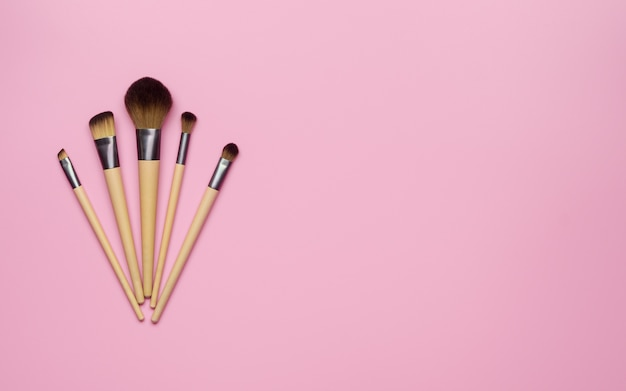 Make up brush sets arranged on pink background, top view with copy space