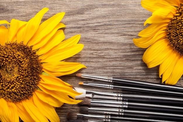 Pennelli per trucco accanto a fiori su fondo in legno