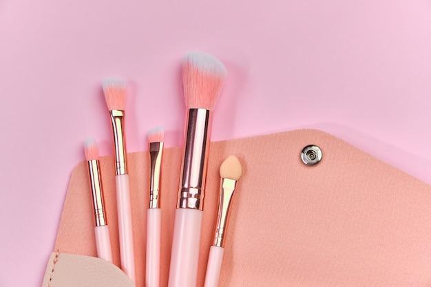 パステルピンクの背景にベージュの化粧品バッグからこぼれるブラシを作ります。上面図。フラットレイ。美容コンセプト。ピンク色の背景、クローズアップビュー、コピースペース。